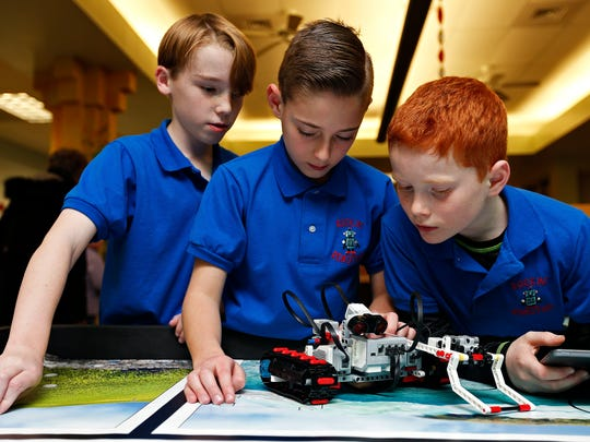 Kenneth Loyd, 10, Keegan Tarsney and Vinny Haning, from left, attempt to get their robot to work during the STEAM Night event held at McBride Elementary School in Springfield, Mo. on Feb. 2, 2017. The robots were acquired by McBride thanks to a grant from the Foundation for Springfield Public Schools.