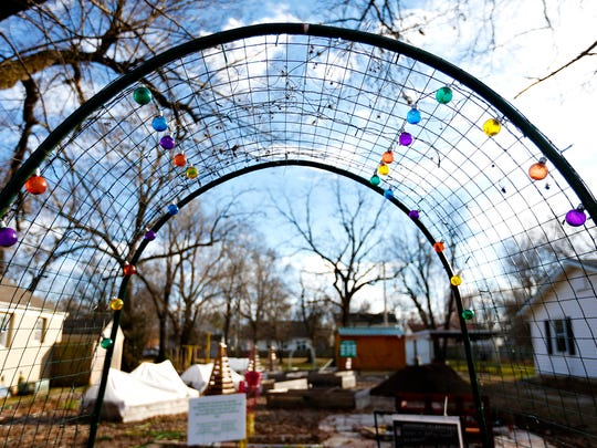 An archway decorated with lightbulbs serves as an entrance to the Delaware Community Garden in Springfield, Mo. on Feb. 23, 2017.