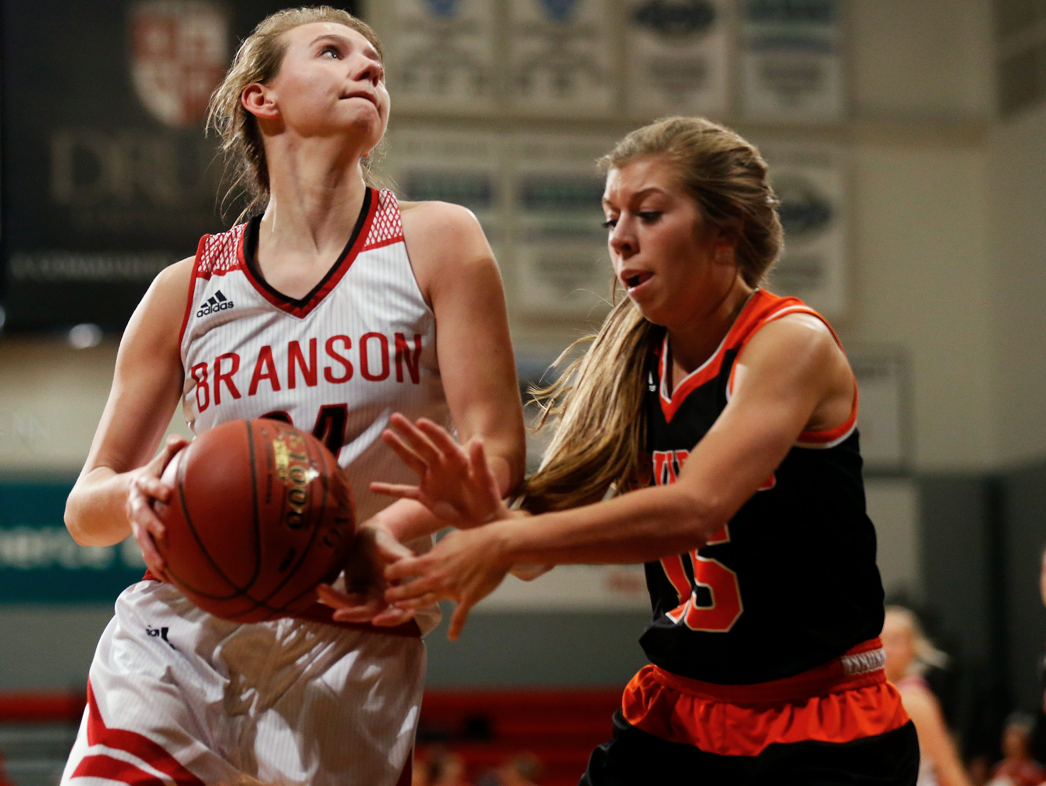 Branson Lady Pirates guard Amanda Kearney (24) drives the ball against Lady Tigers guard Madison Appleberry (15) during third quarter action of the MSHSAA Class 5 sectional playoff game between the Branson High School Lady Pirates and the Republic High School Lady Tigers at the O'Reilly Family Event Center in Springfield, Mo. on March 8, 2017.