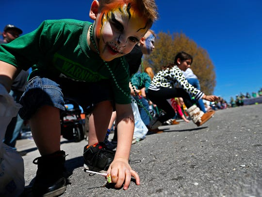 Isaac Ely, 5, reaches for candy during the 2017 St. Patrick's Day Parade in Springfield, Mo. on March 18, 2017.