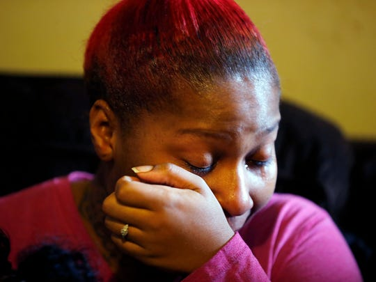 Shanika Jones, 26, wipes tears as she talks about how she and her daughter, Ja'ziah Jones-Keyes, 10 months, were sitting on their couch when a bullet came through the window, just missing them.