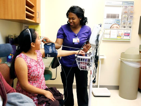 Nurse Shatia Womack checks the vital signs of a patient at the Lincoln Heights Health Center, now part of HealthCare Connect. The Lincoln Heights Health Center marks its 50th year in 2017.