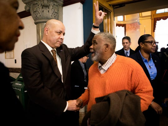 City Manager Harry Black talks with Freeman McNeal, a supporter, Wednesday at Cincinnati City Hall.