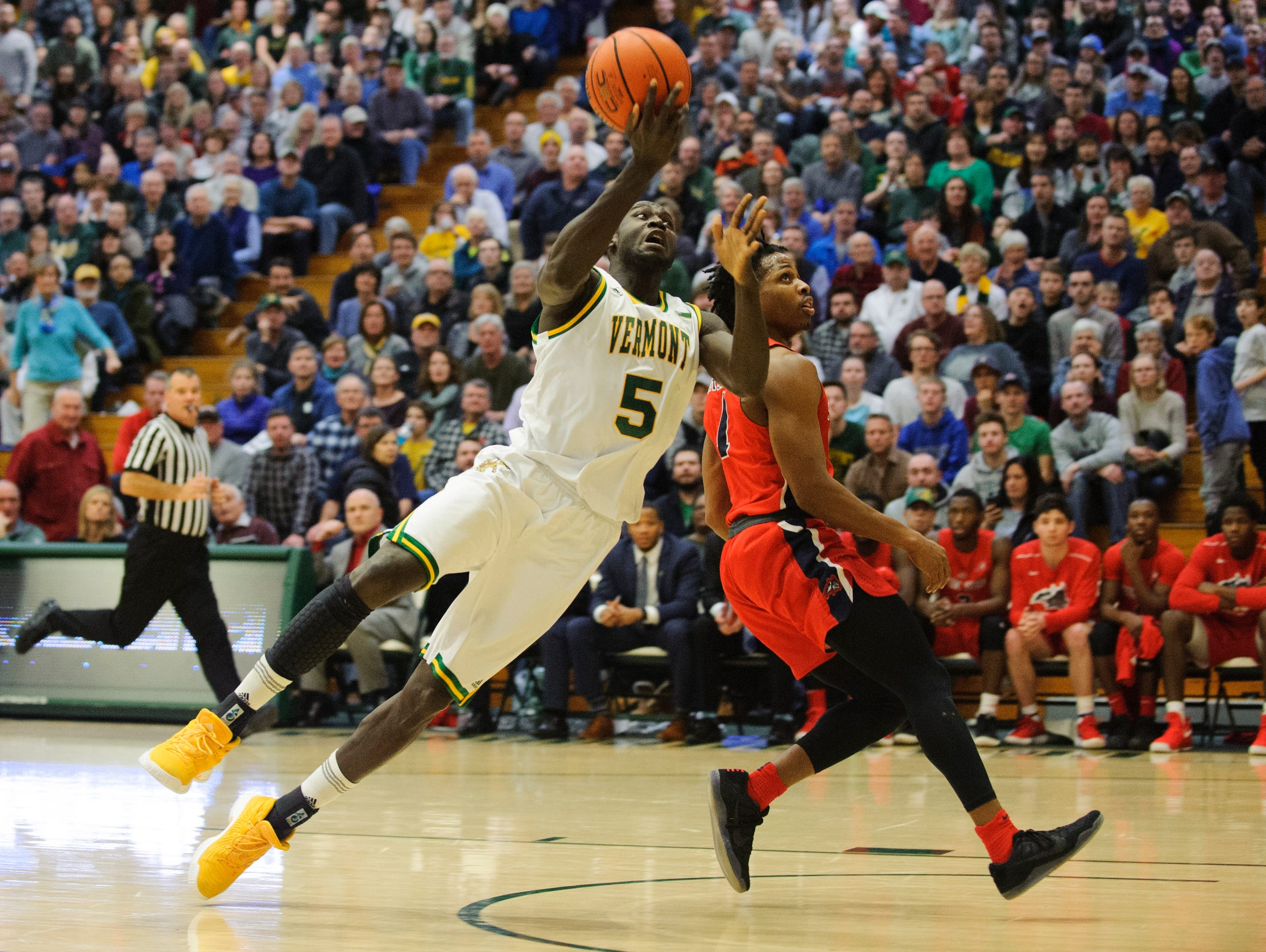 Vermont's Samuel Dingba (5) is fouled during a game last season.