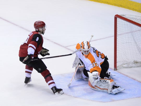 Flyers goalie Brian Elliott is injured as Coyotes center Clayton Keller attempts to score during Saturday's shootout.