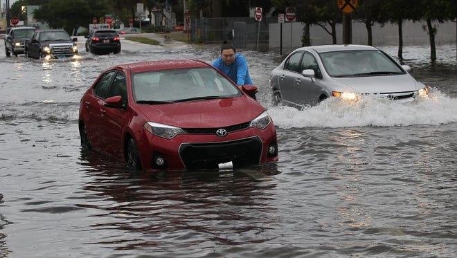 """John Yaung, of Grumpy's Burgers N Beer, a restaurant in downtown Vero Beach, pushes a co-worker's car to higher ground from a parking spot along 21st Street near 14th Avenue after being parked in water almost up to the tops of the tires Tuesday from a heavy rainstorm. """"Little disheartening,"""" Yang said after rescuing his car parked near his co-worker's. """"No one is hurt, that's the important thing."""""""