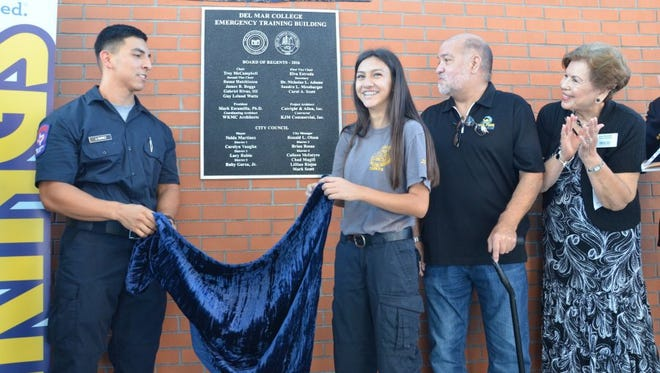 Del Mar College Fire Academy cadets Justin Suarez (left) and Leann Garza assist with the plaque unveiling as regents Gabriel Rivas III, and vice chairwoman Elva Estrada watch during the official opening of the new Emergency Training Building (FEMA Safe Shelter) on the West Campus.