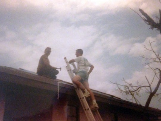 Jay Schlichter, right, helps a neighbor in Homestead, Fla., install a tarp after Hurricane Andrew blew through the town.