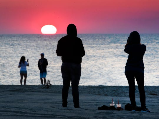Early risers waiting for the Summer Kickoff at Jenkinson's  Boardwalk in Point Pleasant Beach watch the sun rise on May 25, 2018.