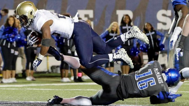 Navy running back Demond Brown dives over Memphis linebacker Wynton McManis to score a touchdown Saturday.