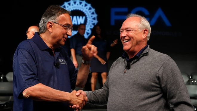 In this July 14, 2015, file photo, Fiat Chrysler Automobiles CEO Sergio Marchionne, left, and  UAW President Dennis Williams shake hands during a ceremony to mark the opening of contract negotiations in Detroit.