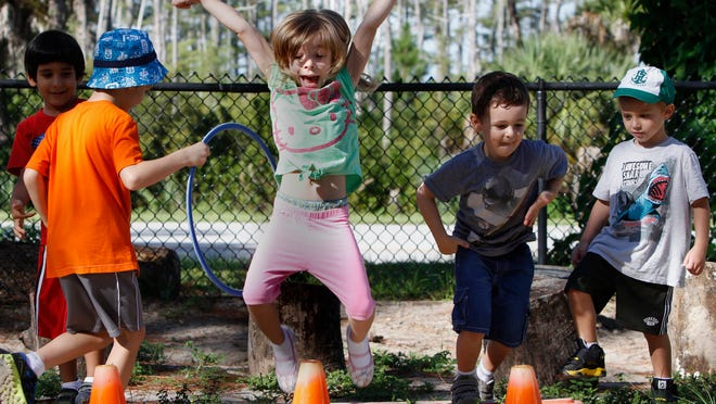 Ainsleigh Babcock, 4, jumps for joy after getting a small hula hoop over an orange cone at the Family Resource Center at FGCU Wednesday.