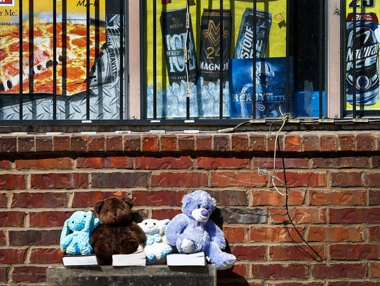 A memorial sits outside the corner store on Tillman,