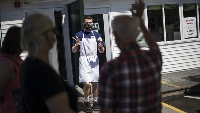 Brendan Kenny serves customers with masks at a Brickley's Ice Cream shop, one of two stores, in Narragansett, R.I., Wednesday, July 29, 2020. The other nearby location closed when teenage workers were harassed by customers who refused to wear a mask or socially distance. Disputes over masks and mask mandates are playing out at businesses, on public transportation and in public places across America and other nations.