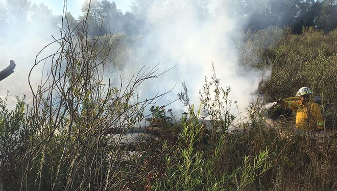 Firefighters work to extinguish a fire at Keizer Rapids Park Monday morning.