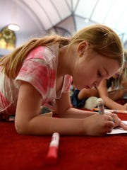 Willa Engler, 6, draws her perfect world, which included