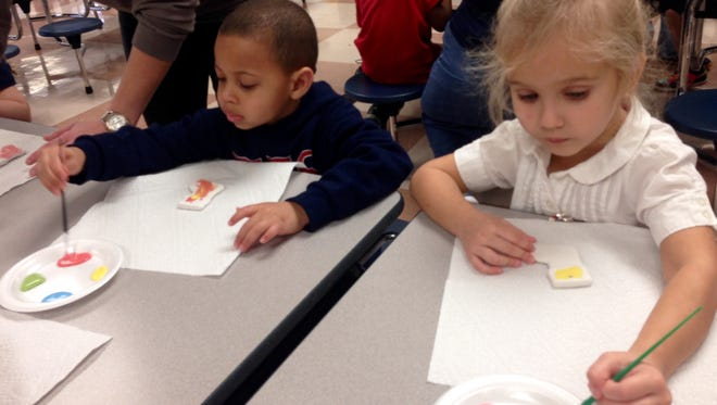 Tioga Elementary pre-K students Johnny Shelvin and Claire Palmer paint ceramic stocking ornaments Friday that will be glazed and fired in a kiln at Funky Fleur de Lis in Alexandria in time to hang on the tree for Christmas.