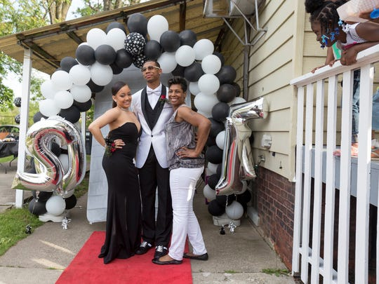 Destiney Drake, 18, left, poses with Michael Green, 18, and his mother LaShaunda Green, before leaving for prom on Friday, May 26, 2017, in Detroit.