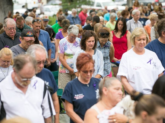 A moment of silence is held Tuesday at Courthouse Square
