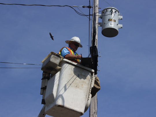 AT&T facility technician Chris Broyles splices fiber to wire along power lines in Panola County (Mississippi). The fiber optic cables will provide broadband access to residents living in rural areas.