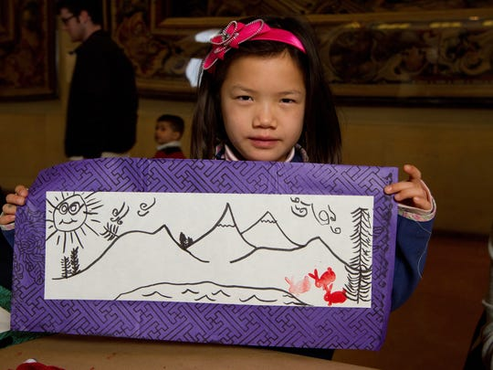 A child shows off her illustration that is part of the Chinese New Year scroll craft.