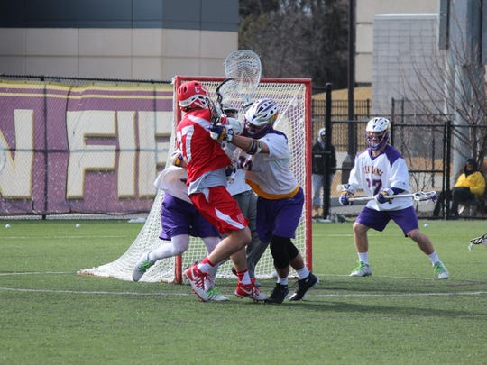 Despite getting crunched by two defenders, John Edmonds of Cornell scores a first-half goal against UAlbany Saturday. The Great Danes beat Big Red in a rematch of their 2015 NCAA game 12-8 in Albany.