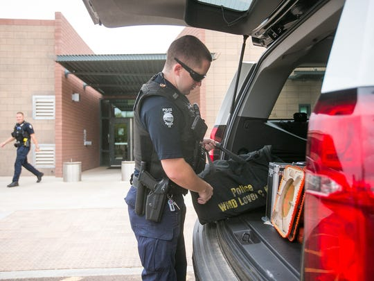 Peoria police Officer Keith O'Connor loads his police vehicle outside the Pinnacle Peak Public Safety Facility before going on patrol in Peoria. A committee of residents developed a lengthy list of ideas to fund with money from a proposed sales-tax increase, including the addition of five police positions to the force.