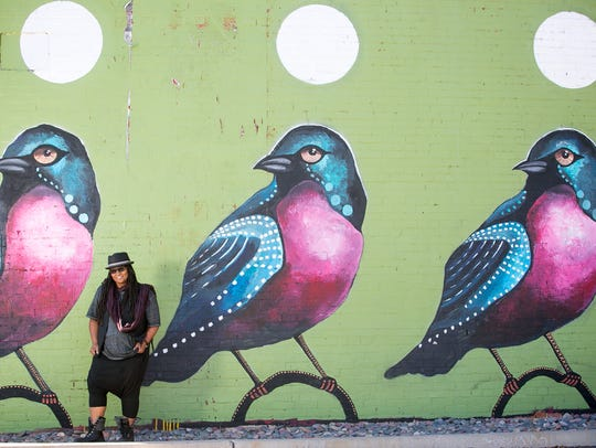 Cole Reed stands next to a mural by artist Lauren Lee