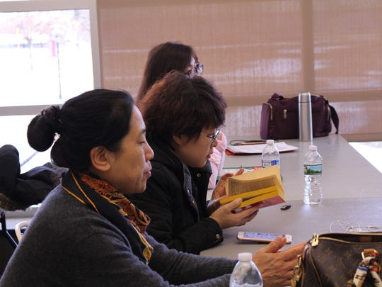Participants review reference materials during a teaching training program at Rutgers for 10 English-language scholars from Jilin University in China.
