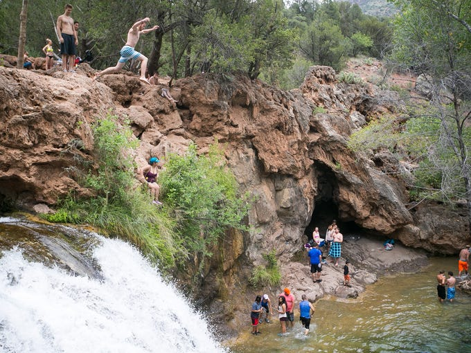 Swimmers jump from a  waterfall at Fossil Creek.