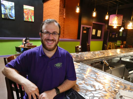 Adam Gold, owner, sits at the counter at the Rochester location of Funk 'n Waffles in 2017.