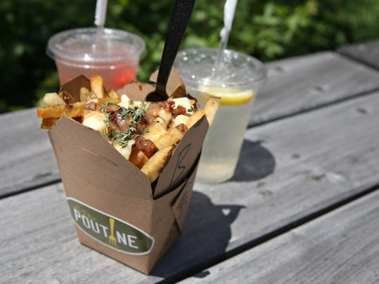 Poutine with bacon from Le Petit Poutine food truck with fruit drinks in downtown Rochester Tuesday, June 13, 2017.