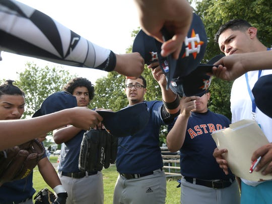 Joel Alicea, 17, center, leads his Astros teammates