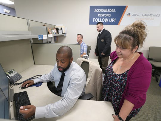 Darius Allen and Stephanie Dardzinski work together on a customer service call in the Customer Care department at Waste Harmonics.