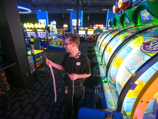 Employee Culley Popham plays an arcade game at the