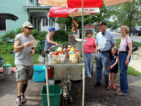 Charlie and Bernadette Clottin have become well known in Pittsford for their Harladay Hots cart, parked on the village's Main Street during lunch hours every summer weekday. Placing their orders are Amy Kastner of Irondequoit, Bob Donahue and Donna Kilker from Fairport, and their granddaughter Jane MacLean of Pittsford.