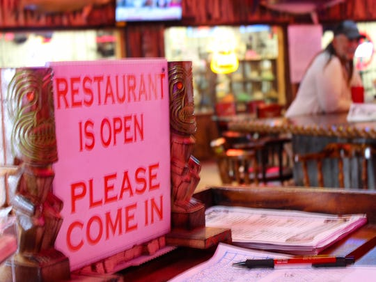 A sign at the hostess' table at Moby Dick's Restaurant makes clear to visitors that the restaurant, heavily damaged in Hurricane Harvey, is open.