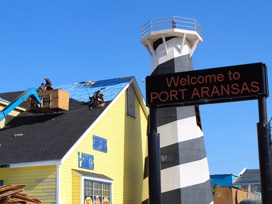 As crews work to repair the roof of Islander Souvenirs, a sign welcomes tourists to Port Aransas, Feb. 1.