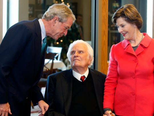 Former President George W. Bush, left, greets evangelist Billy Graham as Laura Bush looks on as they met for a brunch prior to a book signing at the Billy Graham Library in Charlotte, N.C., on Monday, Dec. 20, 2010. (AP Photo/Nell Redmond)