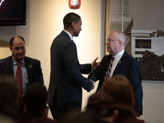 New Missouri State men's basketball head coach Dana Ford shakes hands with MSU president Clif Smart.