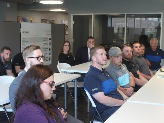 Employees of Summit Solar in Greenville listen Friday