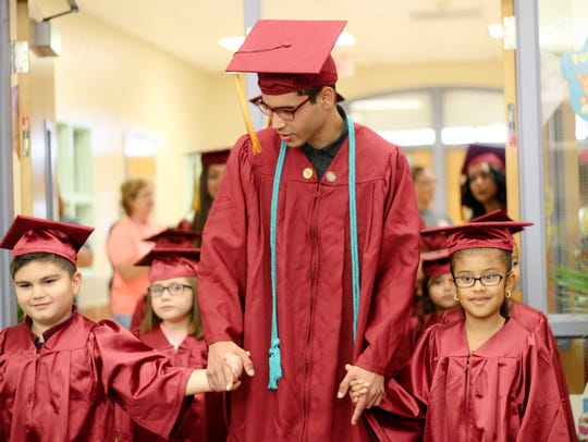 A Tuloso-Midway High School senior walks with two kindergarten