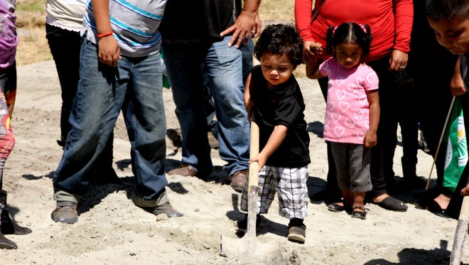 A small child helps with the basketball court groundbreaking ceremonies Thursday at Acosta Plaza.