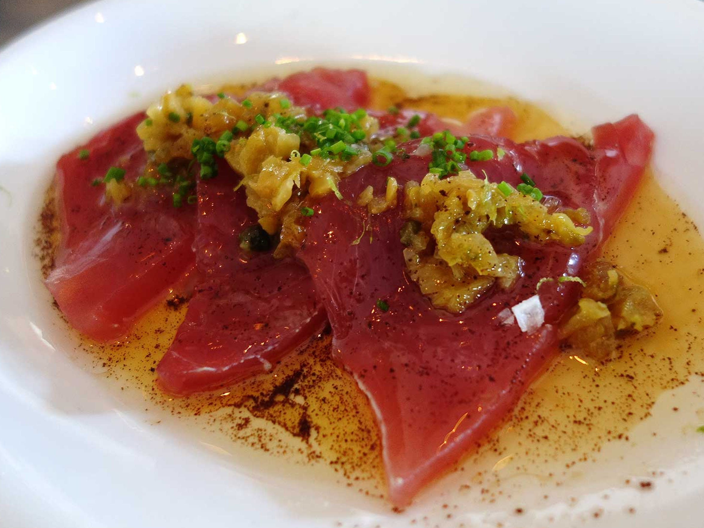 Chula yellowfin crudo with brown butter, fish sauce vinaigrette and golden raisin caper relish at The Gladly's raw bar.