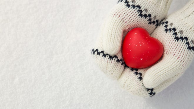 Close up of little girl's hands holding red rubber heart on the snow with copy space