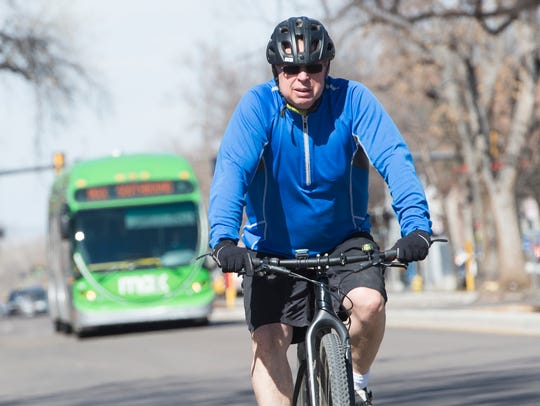 A cyclist is followed by a MAX bus as they move southbound