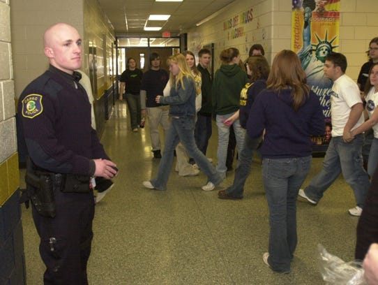 A police officer watches as students walk to classes