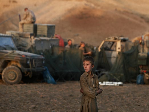 An Afghan boy looks on as German soldiers prepare a temporary camp during a long-term patrol in the mountainous region of Feyzabad in  Afghanistan on Sept. 14, 2009.