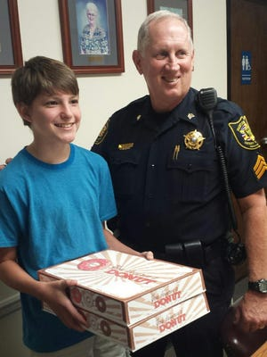 Zachary Smith took photos with Sgt. Joe Gill with Madison County Sheriff's Office on Friday. Smith brought six dozen doughnuts to both the Madison County Sheriff's Office and Jackson Police Department on Friday for 9/11.