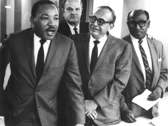 Martin Luther King Jr., left with civil rights leader Timuel Black, far right, circa 1965. The other two men in the photo are unidentified.